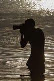 Photographe photographiant dans l'eau, silhouette Photographie stock
