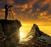Photographe photographiant le coucher du soleil au-dessus du Matterhorn Image libre de droits