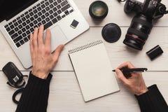 Photographe prenant des notes tout en à l'aide de l'ordinateur portable Photographie stock