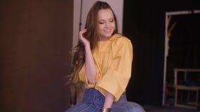 Photographe prenant la photo du mannequin mignon avec de longs cheveux de brune cerly dans le studio Belle pose mod?le femelle banque de vidéos