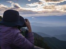 Photographe prenant la photo du paysage à partir du dessus de la montagne Image libre de droits