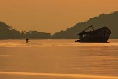 Photographe prenant une photo de vieux bateau d'épave contre l'augmentation du soleil Photo libre de droits