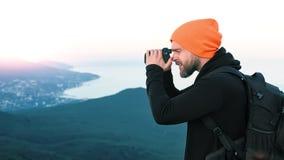 Photographe professionnel masculin de hippie de tir moyen sur la montagne prenant le paysage de mer de photo banque de vidéos