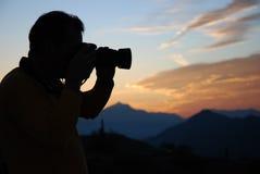 Photographe saisissant le coucher du soleil Photos libres de droits