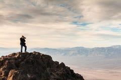 Photographe se tenant sur une roche pendant le lever de soleil à la vue de Dantes image libre de droits