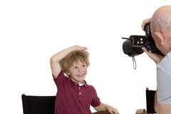 Photographe supérieur cliquant sur l'enfant d'école se reposant sur la chaise au-dessus du fond blanc Photo libre de droits