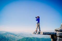 Photographe sur la roche debout Images stock