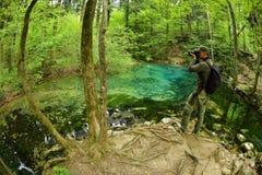 Photographe visitant le bel étang dans les bois photographie stock libre de droits