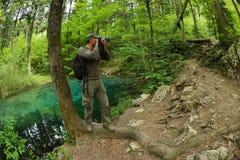 Photographe visitant le bel étang dans les bois photo stock