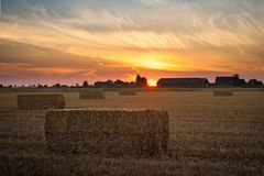 Sunset over the dutch countryside with hay bales royalty free stock photo