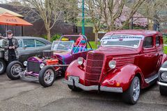 A 1935 Ford Coupe car next to a customized hot rod stock photos