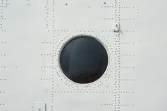 Photographed close-up of metal siding and porthole in military plane in gray Stock Photos