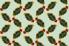 Photographed holly leaves and berries, arranged as regular pattern on light green background. Seamless photograph to be repeated endlessly. Great for printed Royalty Free Stock Photo