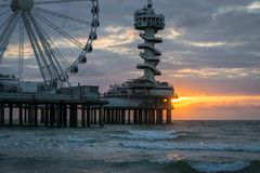 Pier at the dutch coast with Ferris Wheel at sunset royalty free stock image