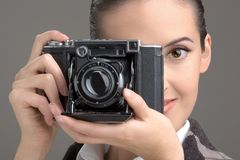Photographer. Close -up of the young woman having control over the antiquarian camera Royalty Free Stock Image