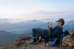 Photographer. Hiker take a picture in mountains Stock Images
