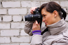 Photographer. Woman photographer on the background of a brick wall Royalty Free Stock Photo