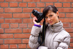 Photographer. Woman photographer on the background of a brick wall Stock Image