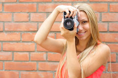 Photographer. Happy woman the photographer on a background of a brick wall Stock Images