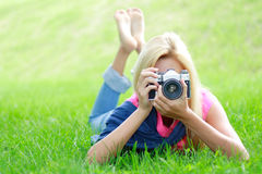 Photographer. Woman the photographer with old camera lays on a grass Stock Images