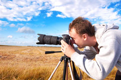 Photographer. Professional photographer taking pictures on field Stock Image