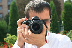 Photographer. Happy photographer in a white shirt pictures of the camera Royalty Free Stock Photo