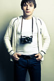 Photographer. Guy with a photocamera on light background. Contrast image Stock Photos