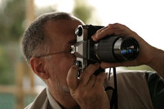 Photographer. Man with an old manual camera taking picture Royalty Free Stock Photos
