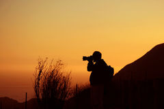 Photographer at sunset. Silhouette of photographer hand holding camera with long lens at sunset Stock Photos