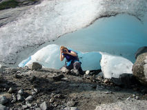 Photographer. The female-photographer photographing a glacier royalty free stock photography