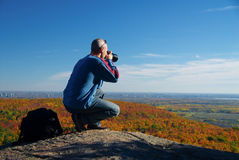 Photographer. Male photographer shooting at the top of a mountain stock photography