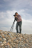 Photographer. On the beach with tropod Stock Photography