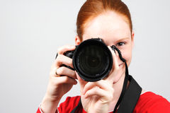 A Photographer. A young and happy female photographer taking a photo with a smile on her face Stock Images