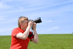 Photographer. Young photographer taking pictures outdoor royalty free stock image