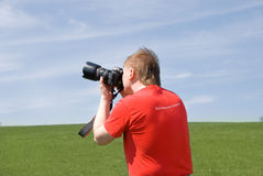 Photographer. Young photographer taking pictures outdoor royalty free stock photography