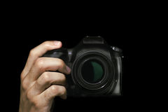 Photographer. Hand with DSLR camera on black background Royalty Free Stock Images