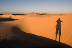 Photographer. The Landscape photographer's long shadow is stretching over the Stockton dunes in Anna Bay, NSW, Australia stock photos