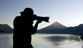 Photographer. Silhouette with lake and volcano on the background Royalty Free Stock Photography