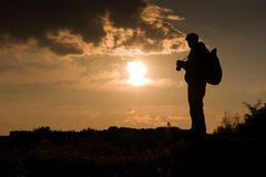 Photographer. Silhouette at sunset in mountains Royalty Free Stock Photo