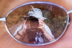 Photographer in action. Mirror image of a photographer taking a picture of a Monarch butterfly on his own hat, using the reflection in the lens a woman's glasses Stock Photography