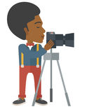Photographer. An african-american photographer standing with camera on a tripod vector flat design illustration  on white background. Vertical layout Royalty Free Stock Images