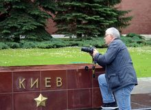 A photographer on the alley of hero cities at the Tomb of the Unknown Soldier in the Alexander Garden of the Moscow Kremlin. MOSCOW, RUSSIA - JUNE 25, 2017: A Royalty Free Stock Photos