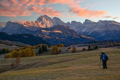 A photographer in Alpe di Siusi at sunrise. Majestic mountains and colorful sky in background, Dolomite Alps, Italy. A photographer in Alpe di Siusi - Seiser Alm Stock Images