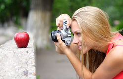 Photographer and apple. The happy woman the photographer photographes an apple Royalty Free Stock Photo
