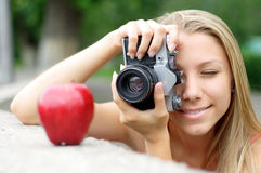Photographer and apple. The happy woman the photographer photographes an apple Royalty Free Stock Photography