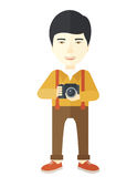 Photographer. An asian photographer holding a camera vector flat design illustration  on white background. Vertical layout Royalty Free Stock Photos