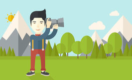 Photographer. An asian photographer taking photo in mountains vector flat design illustration. Horizontal layout with a text space Royalty Free Stock Image