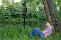 The photographer is asleep while shooting against the background of the river.  Stock Images