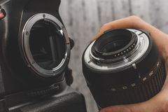 photographer attaches lens to camera royalty free stock photography