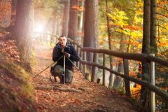 Photographer in autumn forest witw photo camera. Photographer in autumn forest trail on rooty with tripod and photo camera, look at camera Stock Photography
